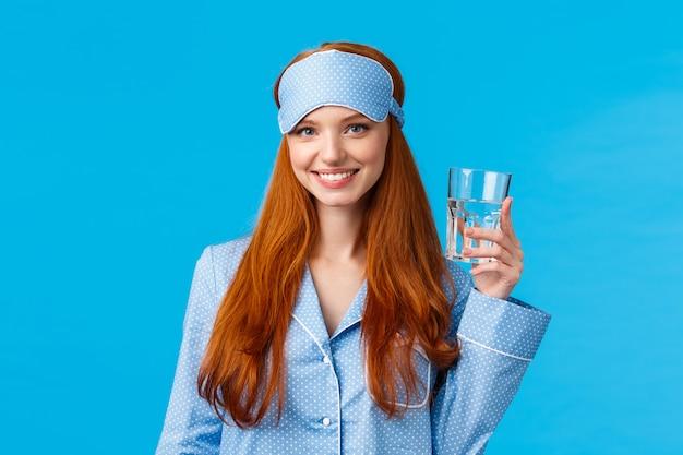Urocza talia glamour rudowłosa kobieta dbająca o zdrowie, zdrowa żywność, woda pitna, nosząca maskę do spania i bieliznę nocną, trzymająca szkło i uśmiechnięta energetyzująca, stojąca niebieska ściana