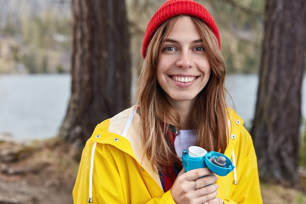 Urocza turystka pije gorący napój z termosu w wiosennym lesie, nosi czerwony kapelusz i żółty płaszcz przeciwdeszczowy, uśmiecha się szeroko do aparatu
