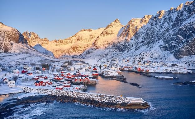 Urocza typowa wioska rybacka na lofotach w norwegii. widok z lotu ptaka. obraz panoramiczny. zapierający dech w piersiach zimowy krajobraz.
