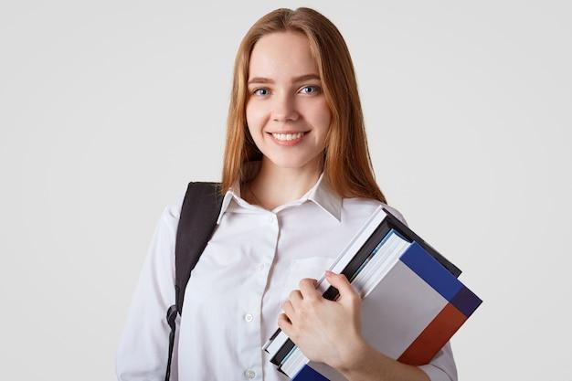 Urocza uczennica o niebieskich oczach, lśniącym uśmiechem, nosi elegancką białą koszulę, nosi książki i plecak, ma długie włosy, przygotowuje się do egzaminu. powrót do koncepcji szkoły
