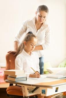 Urocza uczennica odrabia pracę domową, podczas gdy matka na nią patrzy