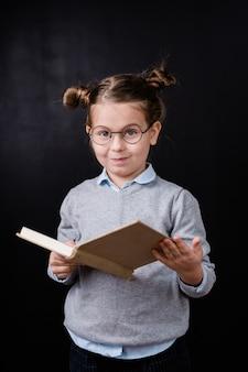 Urocza uczennica podstawowa w okularach, czytanie książki przed kamerą przeciwko czarnej przestrzeni w izolacji