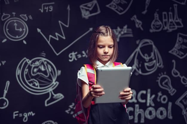 Urocza uczennica przygotowuje się do pójścia do szkoły z plecakiem patrząc na tablet z powrotem do szkoły