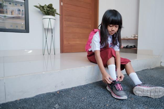 Urocza uczennica szkoły podstawowej zakłada buty