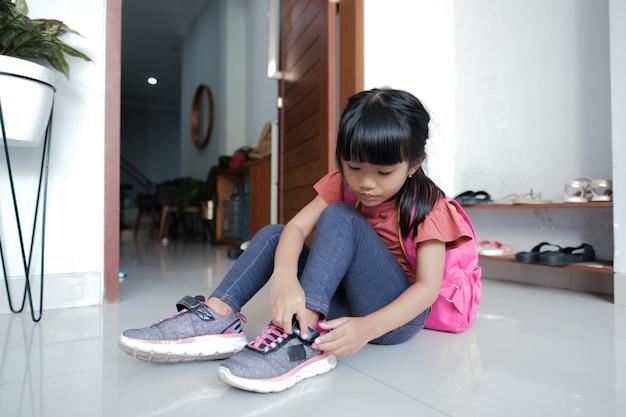 Urocza uczennica szkoły podstawowej założyła buty. przygotowuje się rano do szkoły