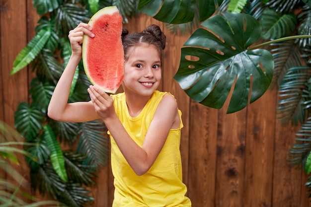 Urocza urocza dziewczyna, śmiejąca się wesoło i trzymająca kawałek arbuza.