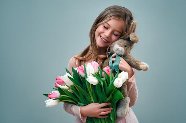 Urocza urocza dziewczynka w różowej sukience trzyma bukiet tulipanów i brązowego pluszowego króliczka na szarej ścianie.