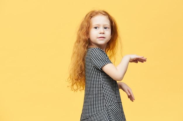 Urocza, urocza europejska dziewczynka w eleganckiej sukience tańczy do muzyki, czując się swobodnie