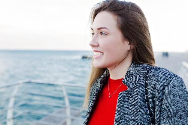 Urocza urocza kobieta o długich jasnobrązowych włosach w szarym płaszczu, aby podziwiać morze i dobrą pogodę na nabrzeżu