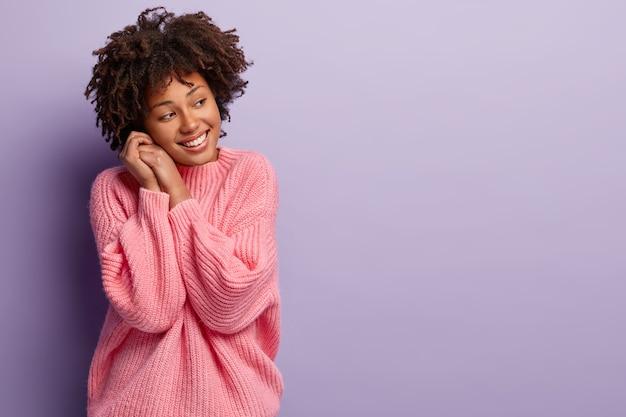 Urocza, urocza kobieta trzyma dłonie blisko twarzy, jest zachwycona, nosi luźny luźny sweter za duży rozmiar