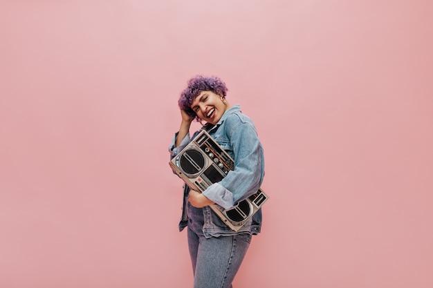 Urocza urocza kobieta z krótkimi kręconymi włosami w złotych okrągłych kolczykach trzyma radio i uśmiecha się
