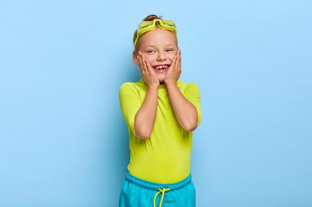 Urocza urocza ruda dziewczyna pozuje w swoim stroju na basenie