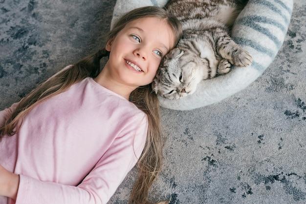 Urocza urocza uśmiechnięta dziewczyna leżąca ze szkockim szarym kotem na dywanie w domu przyjaźń zwierząt