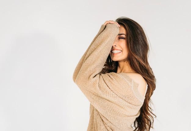 Urocza uśmiechnięta azjatka z długimi brązowymi włosami w beżowym swetrze patrząc na kamery na białym tle