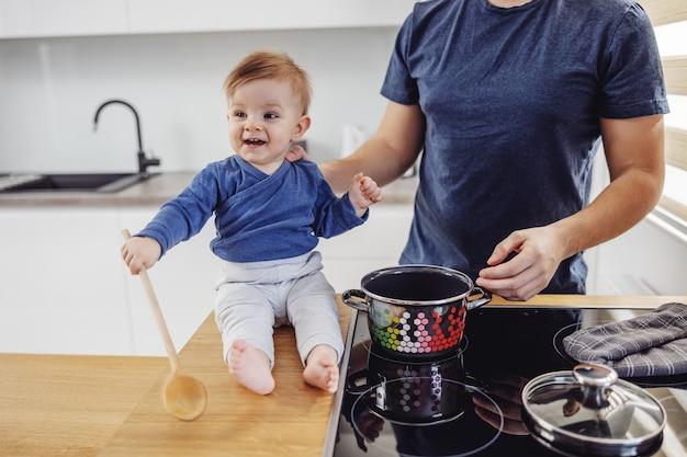 Urocza uśmiechnięta blond maluch siedzi na blacie kuchennym i trzyma łyżkę do mieszania. trzymał go ojciec. przygotowują pyszny posiłek dla całej rodziny.