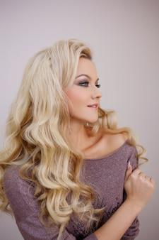 Urocza uśmiechnięta blondynka z luksusowymi blond lokami. piękno włosów