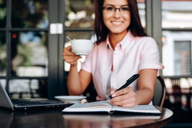 Urocza, uśmiechnięta dziewczyna pisze w zeszycie, zbliżenie