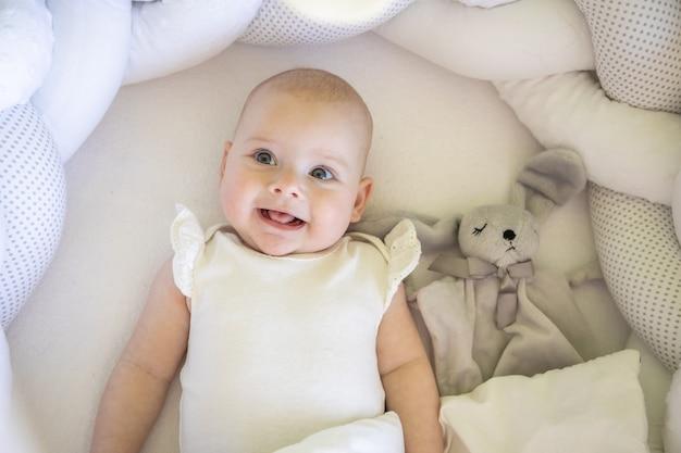 Urocza uśmiechnięta dziewczynka z zabawkowym króliczkiem