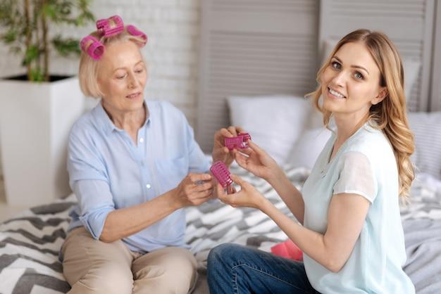 Urocza uśmiechnięta kobieta, patrząc z przodu, podczas gdy jej starsza matka ma zamiar zdjąć z dłoni różowe wałki do włosów