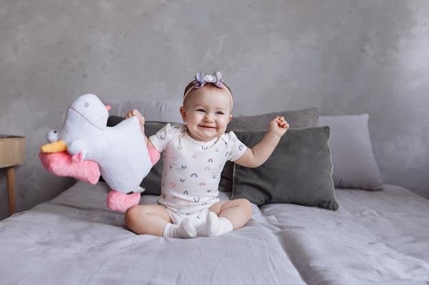 Urocza uśmiechnięta mała dziewczynka z obręczem bawić się z zabawkarskim jednorożcem na łóżku w domu.