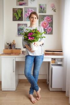 Urocza uśmiechnięta młoda artystka kaukaska trzyma w rękach wazon z piękną kwitnącą dziką różą na tle swojego miejsca pracy z kwiatowymi obrazami. koncepcja sztuki