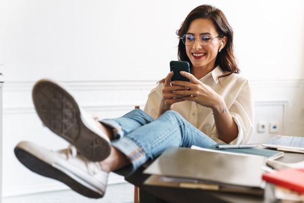 Urocza uśmiechnięta młoda brunetka kobieta relaks przy stole w kawiarni w pomieszczeniu, przy użyciu telefonu komórkowego