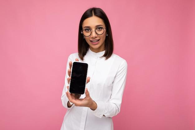 Urocza uśmiechnięta młoda brunetka ubrana w białą bluzkę i okulary optyczne stojąc na białym tle nad różowym tle pokazując telefon komórkowy z pustym ekranem na makieta patrząc na kamery