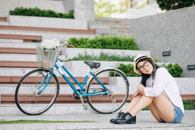 Urocza uśmiechnięta młoda kobieta chiense w dżinsowych szortach siedzi na ziemi ext do swojego roweru i patrząc na kamery