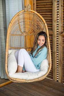 Urocza uśmiechnięta młoda kobieta w biało-niebieskich ubraniach siedząca na wygodnym wiszącym krześle z wikliny rattanowej podczas chłodzenia na tarasie domu