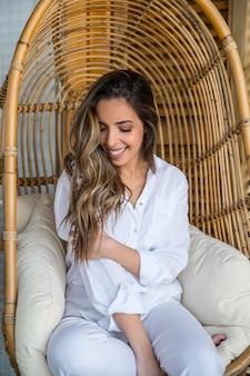 Urocza uśmiechnięta młoda kobieta w białych ubraniach siedzi na wygodnym fotelu wiszącym z wikliny rattanowej podczas chłodzenia na tarasie domu
