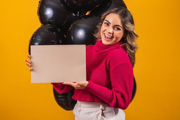Urocza uśmiechnięta młoda kobieta z banerem z wolnym miejscem na tekst i balony na czarnym tle. koncepcja promocji w czarny piątek