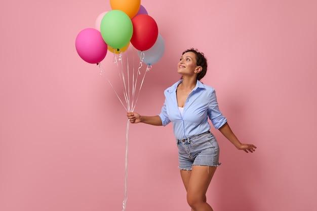Urocza uśmiechnięta młoda rasa mieszana afroamerykanka z bukietem kolorowych tęczowych balonów patrząca w górę i bawiąca się, ubrana w dżinsowe szorty i niebieską koszulę na różowym tle ściany z kopią miejsca