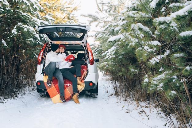 Urocza uśmiechnięta para siedzi w bagażniku samochodu w zimowym lesie