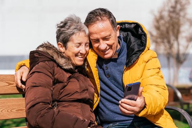 Urocza uśmiechnięta para starszych za pomocą smartfona siedząc na ławce w parku selektywna ostrość