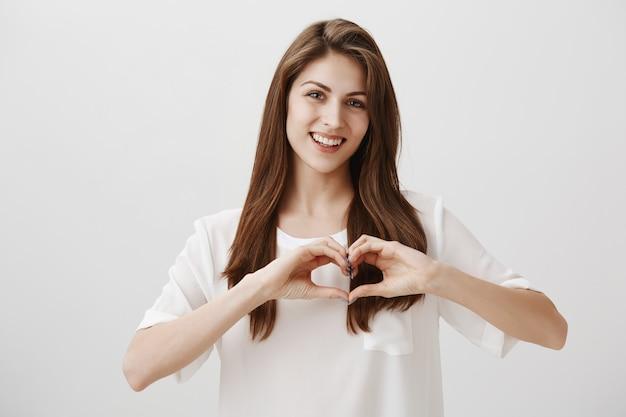 Urocza uśmiechnięta szczęśliwa kobieta pokazuje gest serca