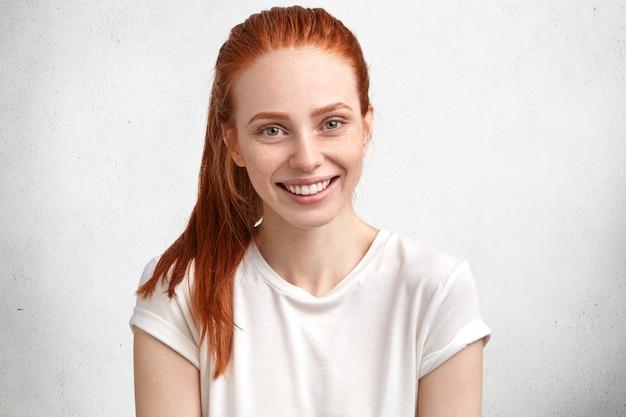 Urocza uśmiechnięta, zachwycona młoda modelka z rudymi włosami i piegami na twarzy, ubrana w swobodną białą koszulkę, wyraża pozytywne emocje