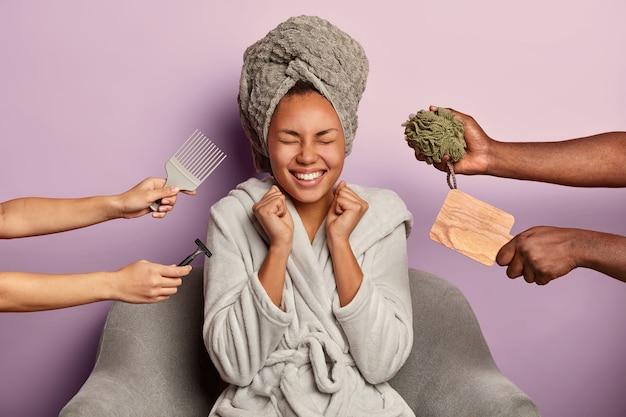 Urocza uszczęśliwiona kobieta w domowych ubraniach ma zdrową skórę zaciska pięści ze szczęścia