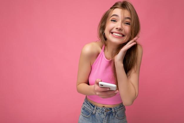 Urocza uszczęśliwiona młoda blondynka ubrana w różowy top poising na różowym tle