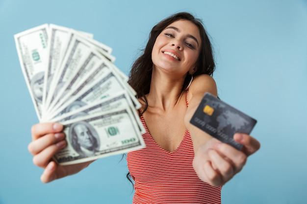 Urocza wesoła dziewczyna ubrana w letnie ubrania, stojąc na białym tle nad niebieskim, pokazując banknoty i kartę kredytową