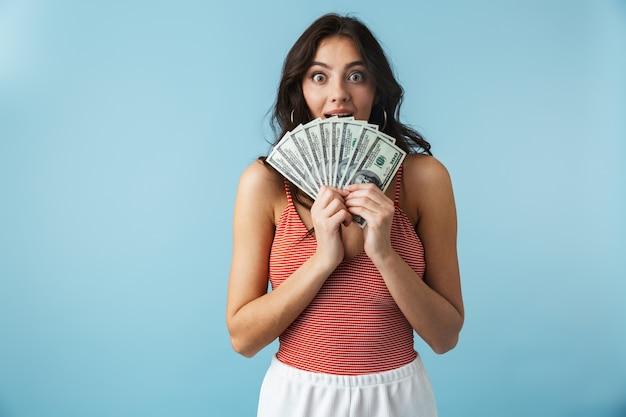 Urocza wesoła dziewczyna ubrana w letnie ubrania, stojąc na białym tle nad niebieskim, pokazując banknoty pieniędzy