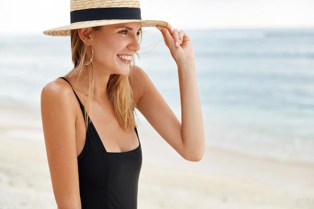 Urocza wesoła kobieta ubrana w czarne bikini i słomkowy kapelusz, pozytywnie patrzy w dal, stojąc na tle oceanu, podziwia niekończący się horyzont. zrelaksowane kobiece spacery na plaży na świeżym powietrzu w pobliżu morza