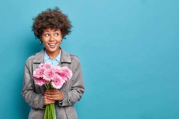 Urocza wesoła kobieta z bukietem różowych gerber świętuje wiosenne wakacje ubrana w model szarej kurtki na tle niebieskiej ściany