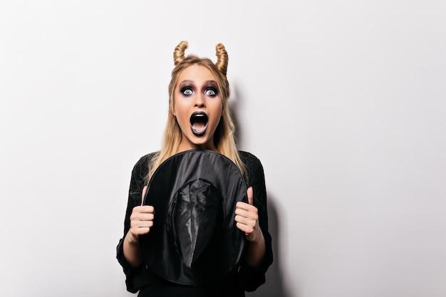 Urocza wiedźma pozuje z zaskoczonym wyrazem twarzy. przestraszona dziewczynka kaukaski świętuje halloween.