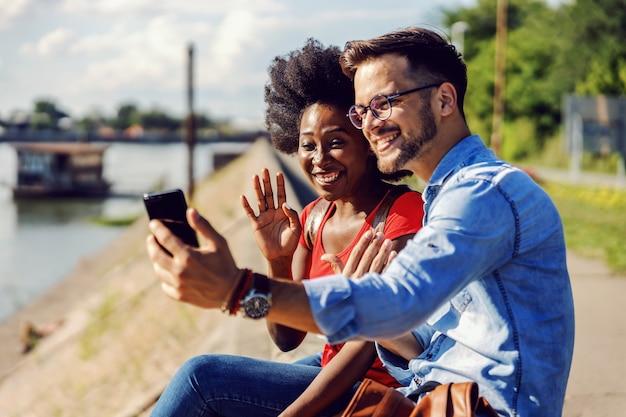 Urocza wielokulturowa para siedzi nad rzeką i prowadzi rozmowę wideo z przyjaciółmi przez smartfona.