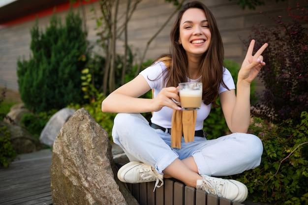 Urocza wolna młoda kobieta w swobodnym wyglądzie pije kawę na ulicy.