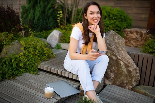Urocza, wolna młoda kobieta w swobodnym wyglądzie pije kawę siedząc w letnim parku.
