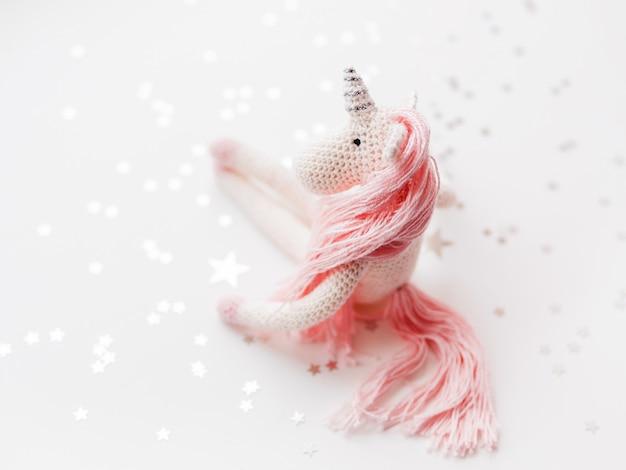 Urocza wróżka jednorożca z różową grzywą i ogonem wykonanym z nici.