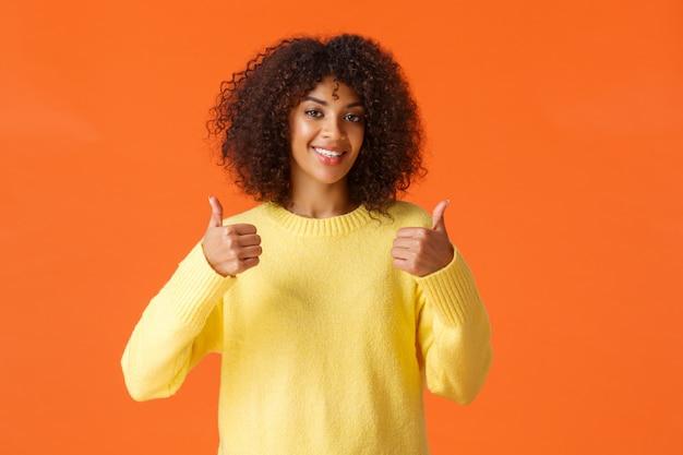 Urocza, wspierająca afroamerykańska kobieta z uśmiechem w talii, zadowolona z doskonałego pomysłu, strzelająca kciukiem do góry i uśmiechnięta, zgadza się z tobą, daje pozytywną odpowiedź, poleca produkt, pomarańczowa ściana