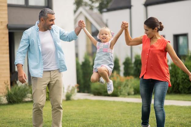 Urocza zabawna córka. rodzice podnoszą swoją uroczą zabawną córkę podczas zabawy na zewnątrz w pobliżu domu