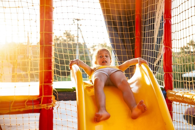 Urocza zabawna szczęśliwa dziewczyna siedzi na jasnożółtej zjeżdżalni w wielokolorowym centrum rozrywki i przygotowuje się do zejścia w słoneczny dzień